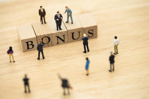 ミニチュアの人々収益を待っているビジネスマンビジネスの利益