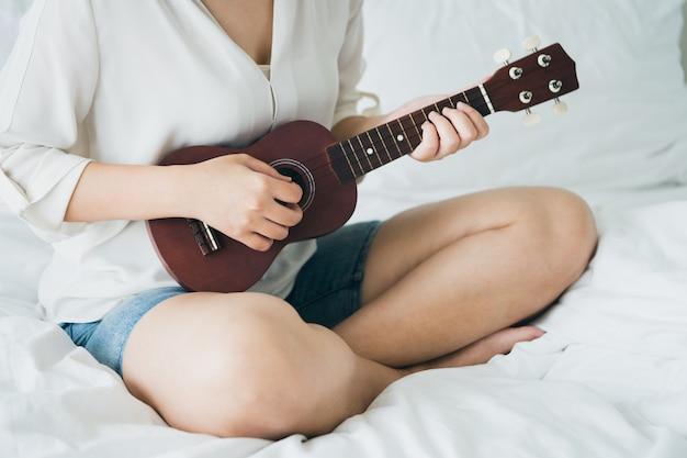 アジアの女の子朝起きてからギターを弾きます。明るく感じさせる
