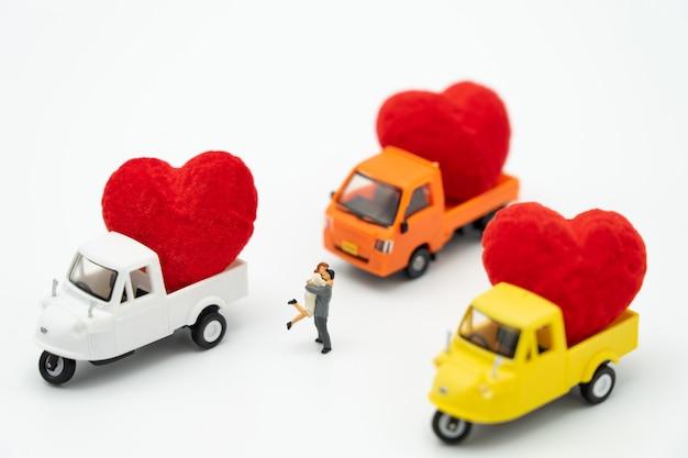 赤いハートで立っているカップルのミニチュアの人々は愛の約束です。