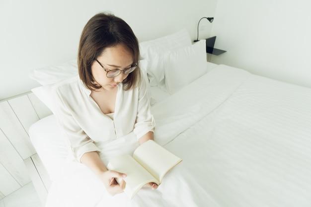 Азиатская девушка читать книги после пробуждения по утрам. это заставляет вас чувствовать себя ярко