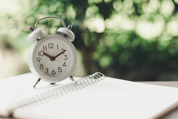 Старинный белый будильник на ноутбуке. время отдыхать. используя в качестве фона