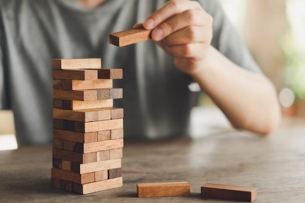 リスクが発生します。木のテーブルにブロック木のゲームをプレイするエンジニアの手