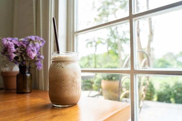 背の高い透明なガラスにココア飲料を混ぜ合わせた、窓際に置いた爽やかな