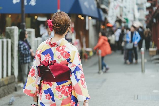 東京の浅草寺の前に日本の着物姿で立っている若い女の子