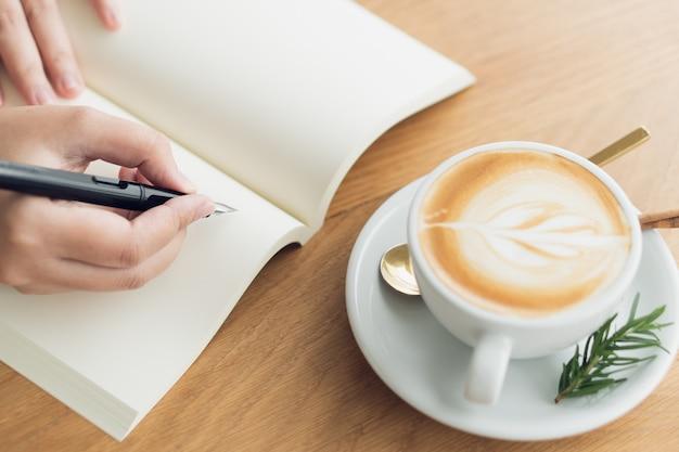 ビジネスの女性、旅行者、記事の作家空の本にテキストを書くためにペンを持ってください。