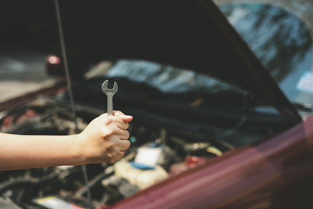 機械エンジニアの手が車のスカートを開いて車のオイルレベルをチェックします。