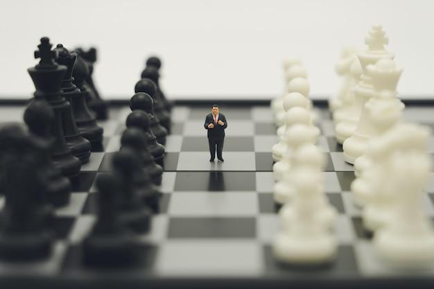 チェスの駒とチェス盤の上に立ってミニチュア人ビジネスマン