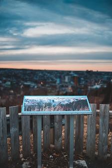 日没時に水の体の近くの茶色の木製フェンス
