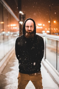 Человек в черном пуловере с капюшоном куртки