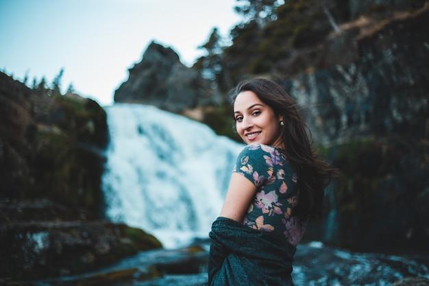 Женщина смотрит через плечо с водопадом на заднем плане