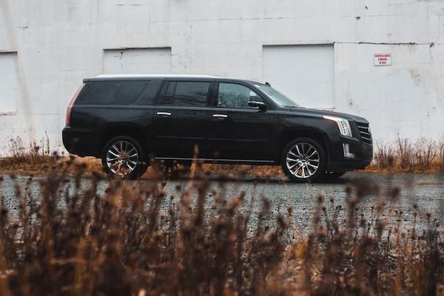 Черный универсал припаркован на тротуаре возле здания