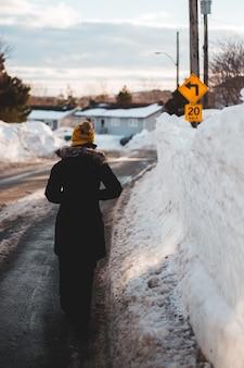 昼間に雪に覆われた道路に立っている黒いコートの人
