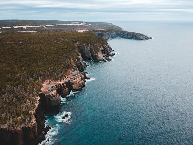 昼間の青い海の横にある茶色と緑の山