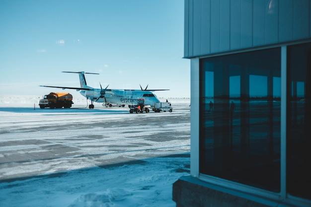 昼間の建物の前のトラックの近くの飛行機