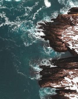 日中の水域の横にある茶色の岩の形成