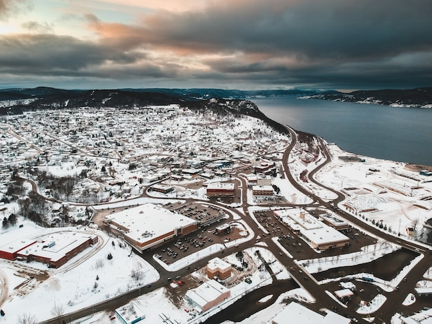 黄金の時間の間に曇り空の下で水の体の近くの雪に覆われた住宅の航空写真