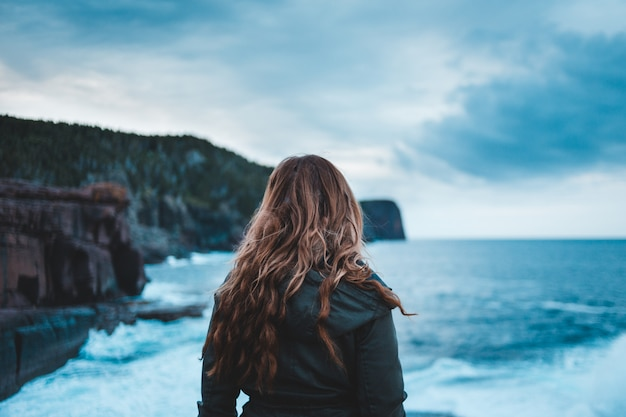 Женщина стоит возле моря