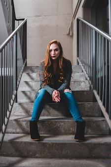 Женщина в черном свитере и синих джинсах сидит на лестнице