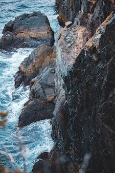 日中の水域の横にある茶色のロッキーマウンテン