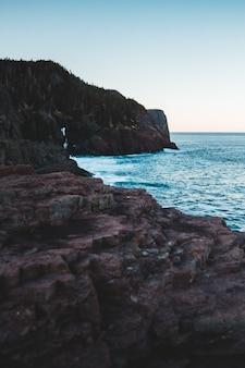 昼間の海の横にある茶色の岩の形成