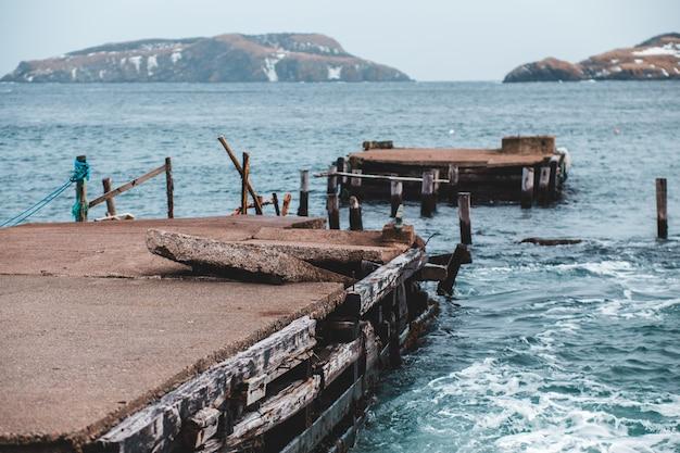 昼間は青い海に茶色の木製ドック
