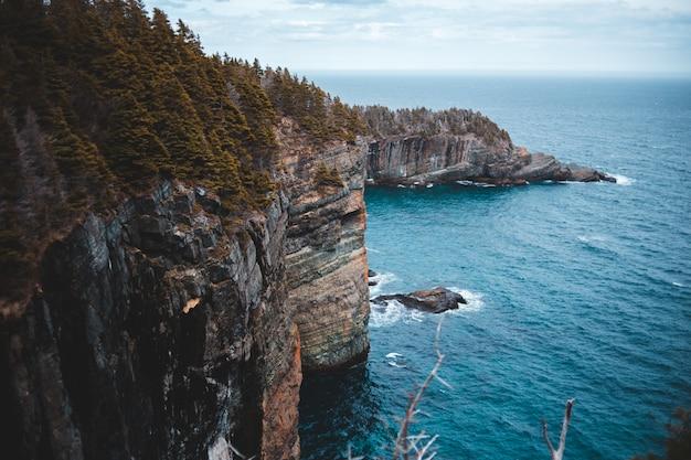 昼間の青い海の横にある茶色の岩の形成
