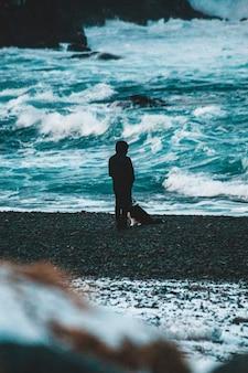 昼間に海岸を歩く黒いジャケットの男