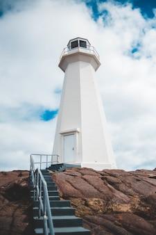 昼間に白いコンクリートの灯台に向かって行く空の階段