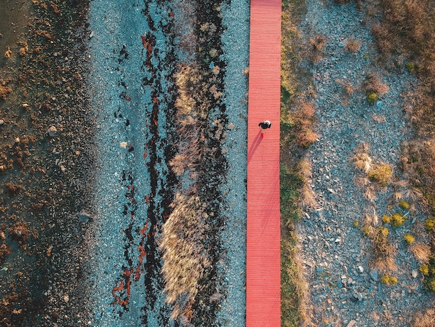 Фотография вида сверху человека, идущего по оранжевой тропе
