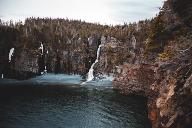 Коричневая скалистая гора у водоема днем