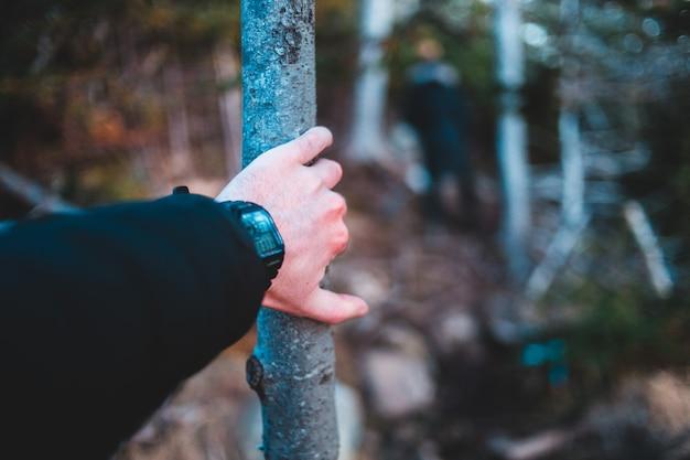 茶色の木の棒を持って黒い時計を着ている人