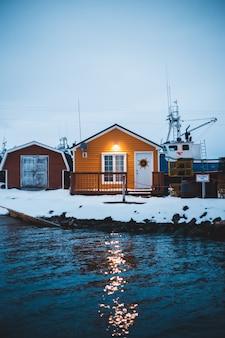 水の体の近くの照明付き屋外ランプを示すオレンジの木造住宅