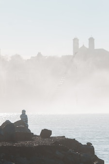 Человек сидит на скале возле водоема