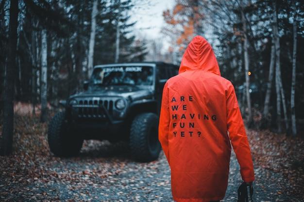 木の横にある赤いコートの上を歩く人