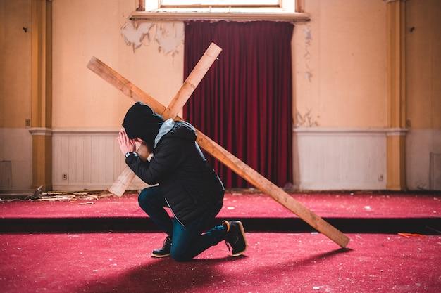 木製の十字架を持つ黒のパーカーと青いパンツの男