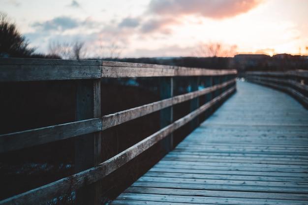 日没時に水の体に茶色の木製の橋