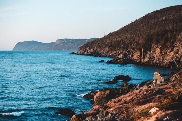 昼間の青い空の下で青い海の横にある茶色のロッキーマウンテン