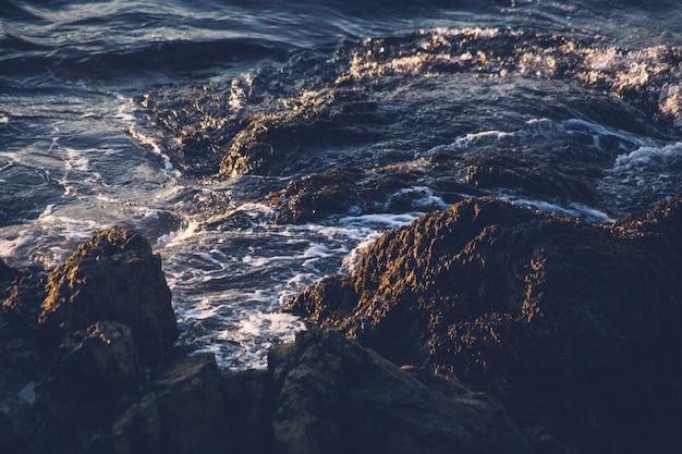 昼間の水の体の横にある茶色と黒の岩の形成