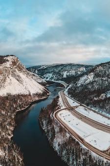 日中は雪に覆われた川と山の近くの道路