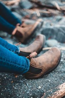 青いデニムジーンズと茶色の革の靴の人