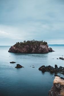 日中の白い雲の下の海の緑と茶色の岩の形成
