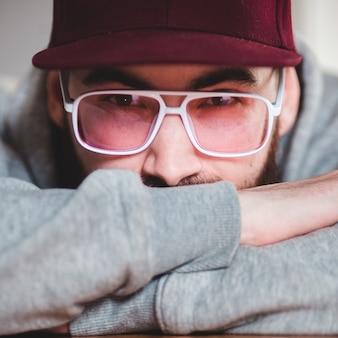 Человек в сером свитере в черных оправах и красной шапочке