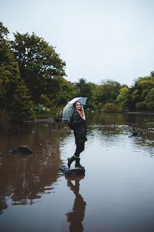 白い空の下で傘を持つ女性