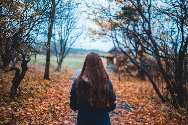 裸の木の横の未舗装の道路を歩く女性