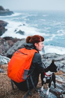 Женщина сидит на возвышенности рядом с собакой