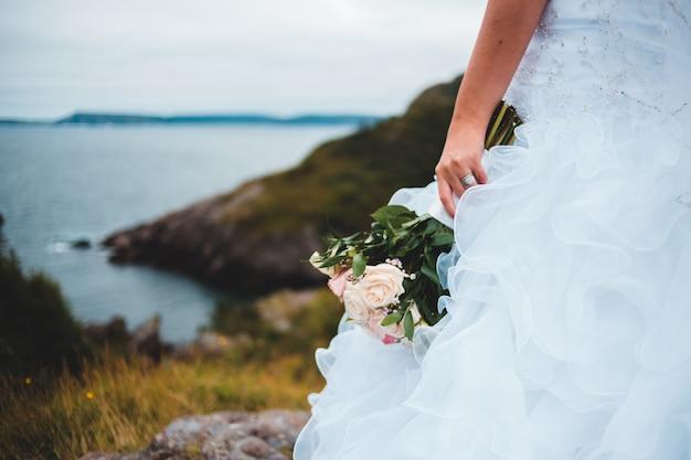 花の花束を保持している白いウェディングドレスを着た女性