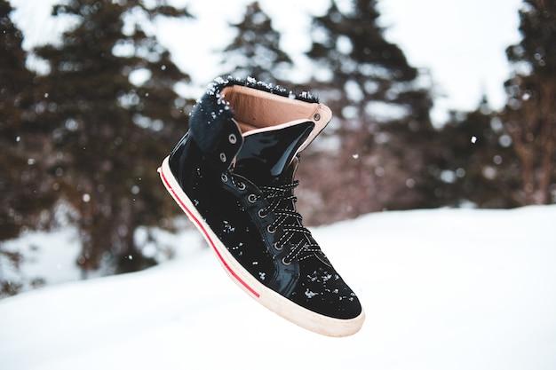 雪に覆われた地面に黒と白のバスケットボールシューズ
