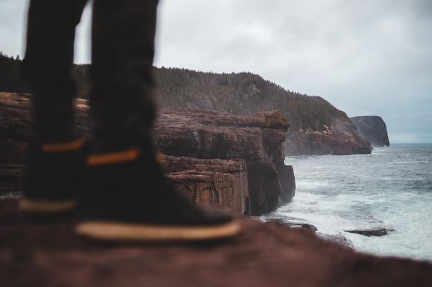 海の波の背景に男の靴