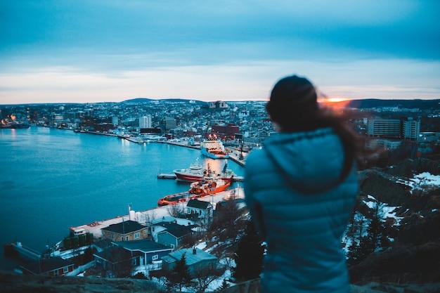 町と水を眺めながら立っている女性