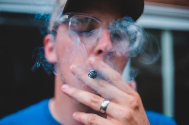 タバコを吸ってメガネの男
